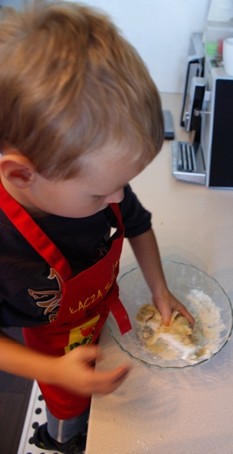 Młody w trakcie wyrabiania ciasta na kruche ciasteczka